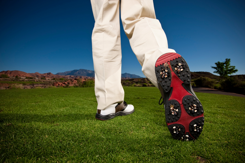 Low angle close-up of the bottom of a golfer's modern, new golf shoe on the green right after the swing.