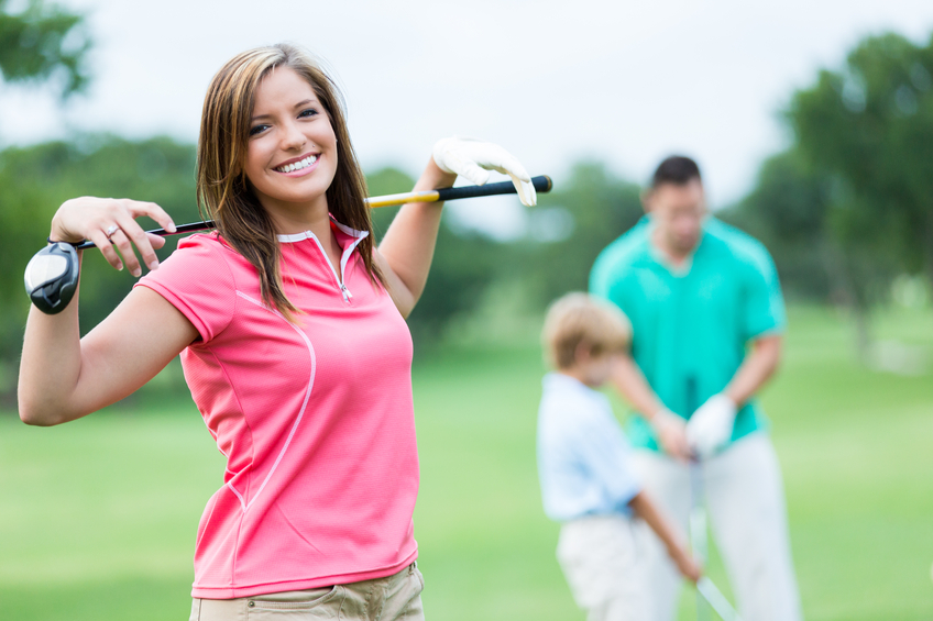 Pretty mid adult woman smiles confidently as she plays golf with her family. He is wearing a golf shirt and is holding a golf club stretched behind her neck. Her husband and son are playing golf in the background.